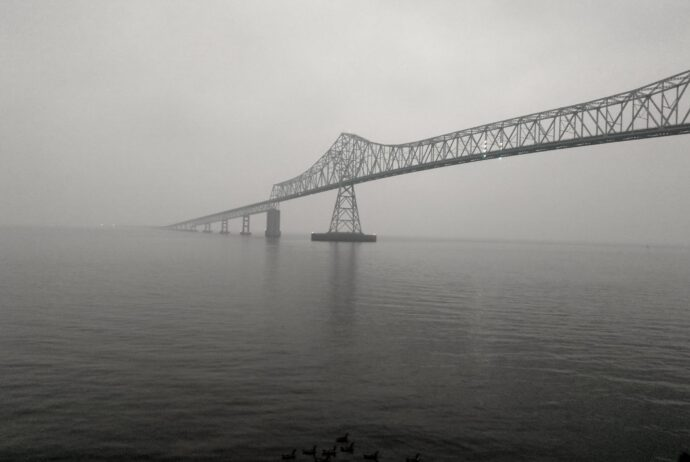 an iron bridge crossing the Columbia River at Astoria Oregon fades into the grey bank of ash and smoke