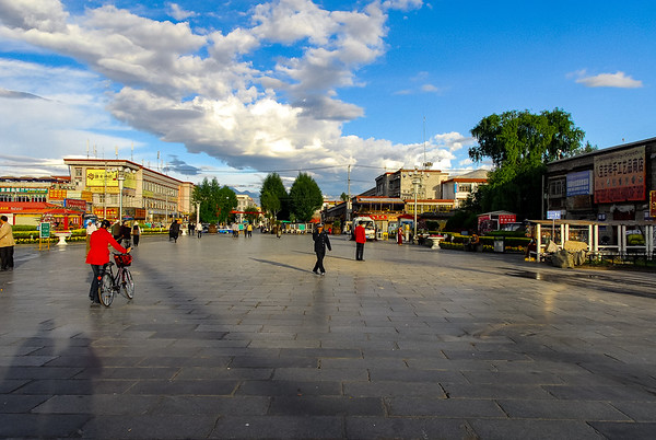 Large flagstone plaza with shops and buildings on either side receding view toward trees with scattered people in the early morning light.