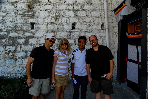 Photo of Tim, Corinne, our guide Dorje, and Patrick in front of a stone call with a Tibetan cloth door to the right.