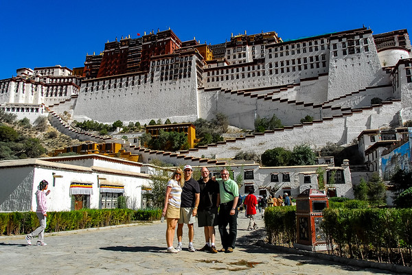 Photo of our travelers in front of a rising shot of the Potala Palace with whitewashed walls, zigzag stairs, and red upper walls and roof.