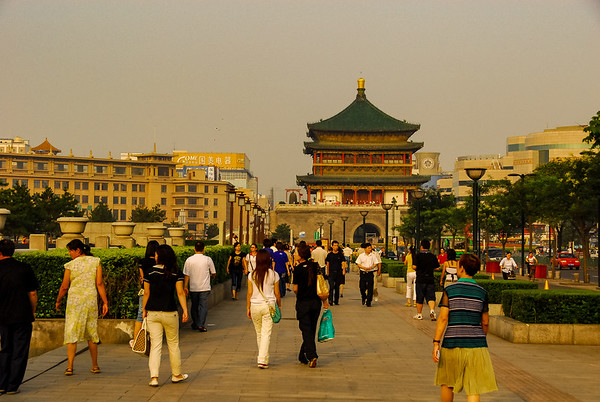 A view of a long walkway with many people casually walking about and in the distance a large pagoda style building with a green roof and red accents.