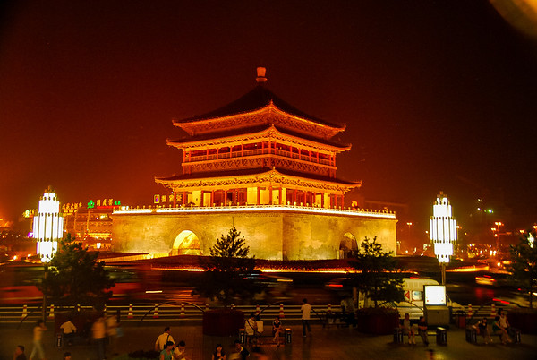 A night time view of the pagoda-style Bell Tower with light rising up and two striking tall lamps on either side of the building.