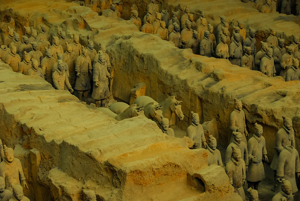 A photo of thick walls forming ranks moving down left to right on a diagonal through the picture. Between the thick walls are ranks of ancient chinese warriors in uniform with some horses, all made of terracotta with a gray-green cast.