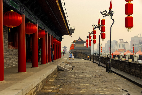 A view down the wall of Xi'an with building on the left with red pillars and lamps lining the right side.